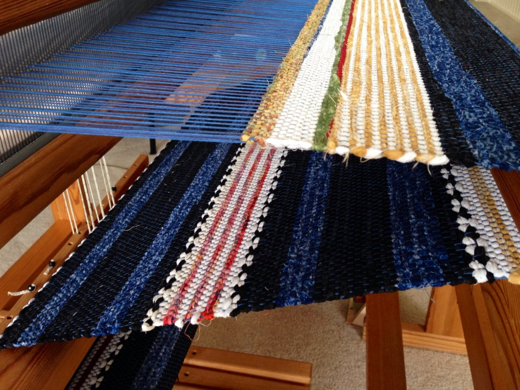 Rag Rug on the loom. Striped hem is followed by scrap strips to secure the wefts.