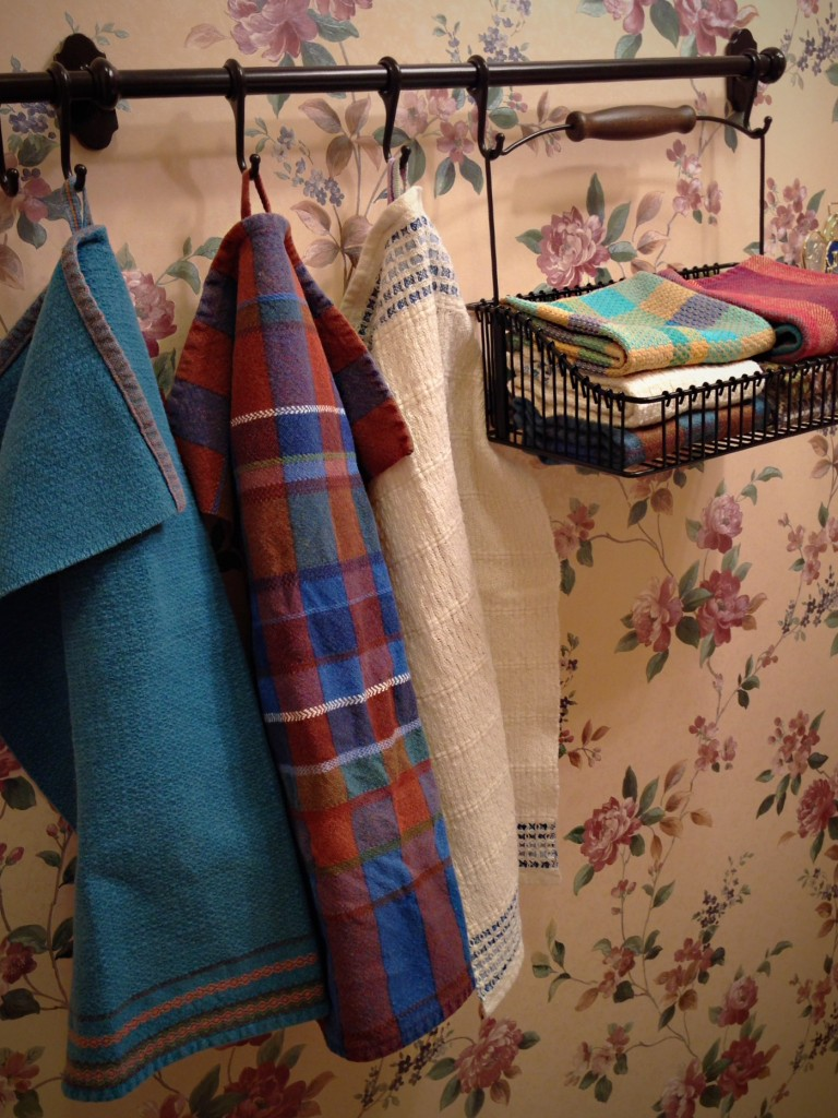 Ikea basket and hooks hold handwoven towels for guests.