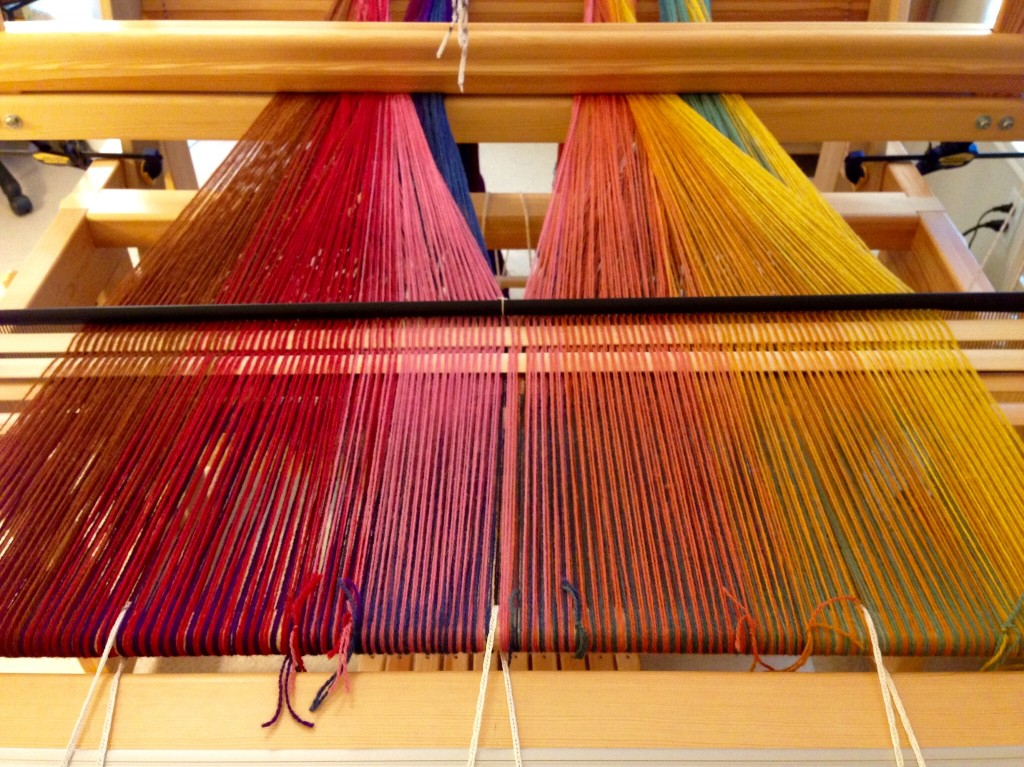 Upper layer of double weave is spread on the loom.