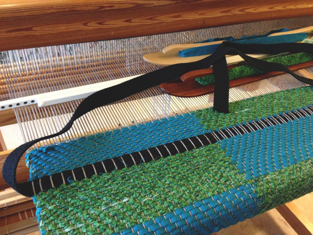 Weaving bag handles into the rag rug bag.