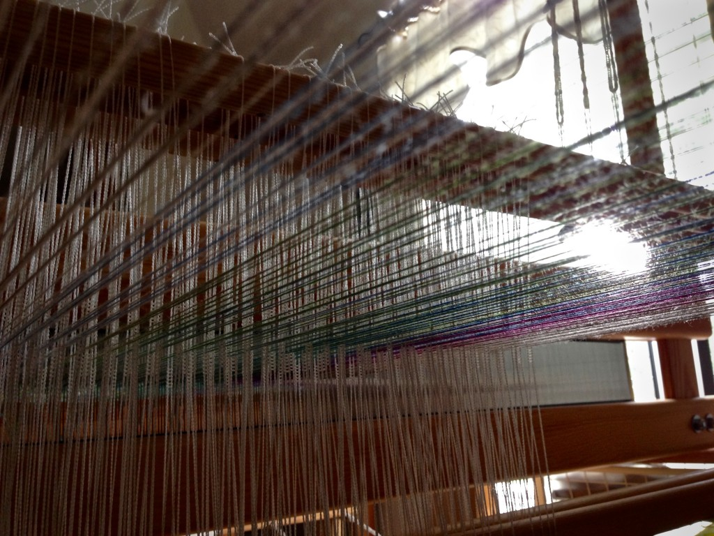 "Tying up treadles in the ""playhouse"" under the warp."