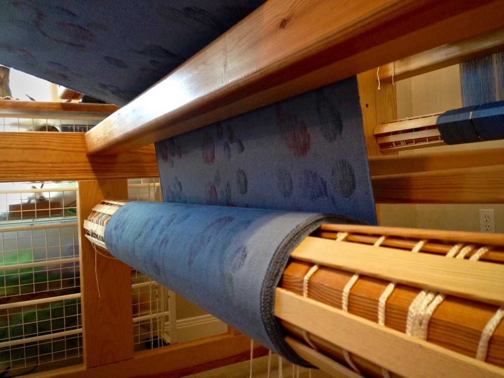 Printed fabric collects on the cloth beam.