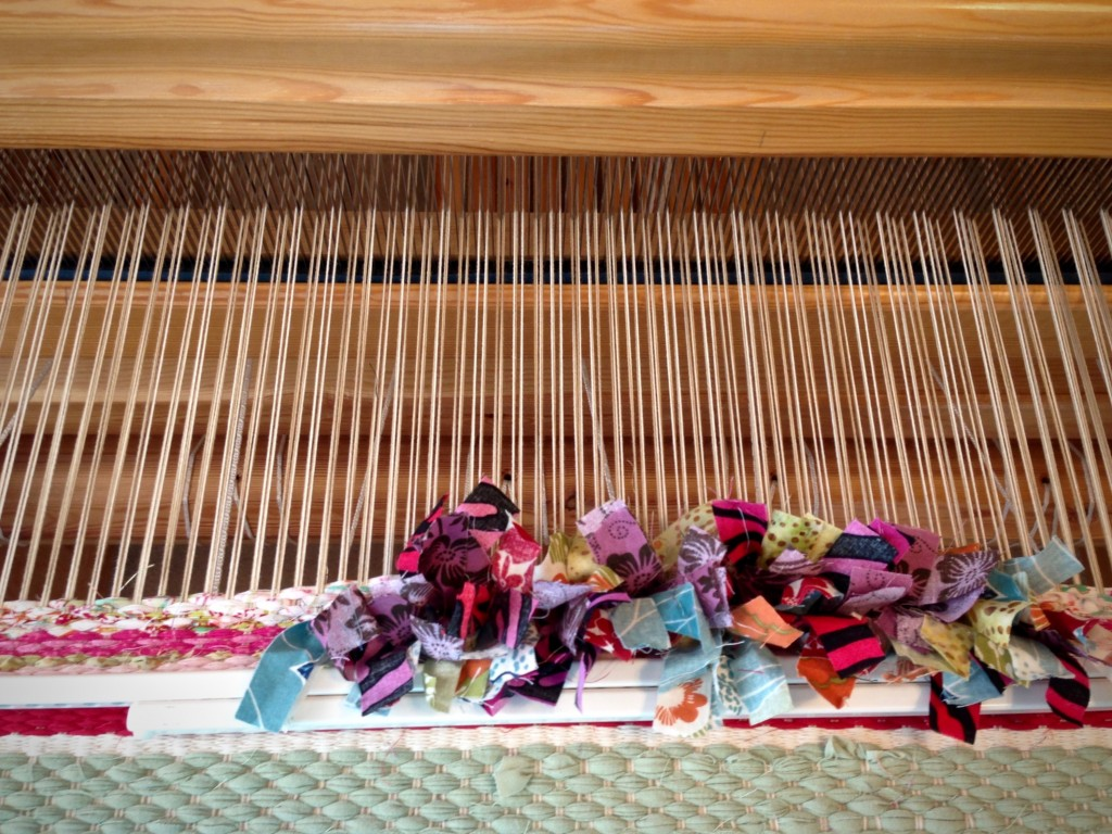Beginning sample of rag rug weaving with rya knots.