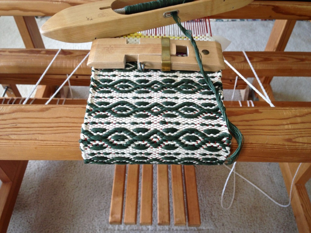 Mug rug being woven with string yarn. Customized mini temple.