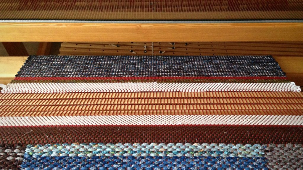 Warping slats as spacers between rag rugs.