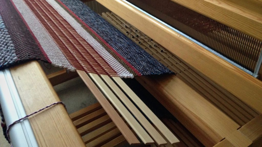 Warping slats are used as spacers between two rag rugs on the loom.