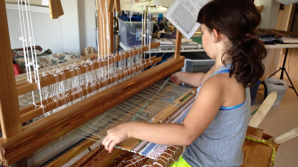 Young weaver at the loom making her first rag rug.