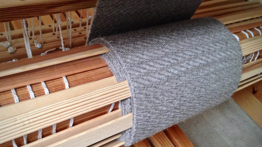 Woven fabric at the cloth beam. Warping slats between the scarves keeps the unwoven yarn (for fringe) from slipping off the cloth layers at the sides.
