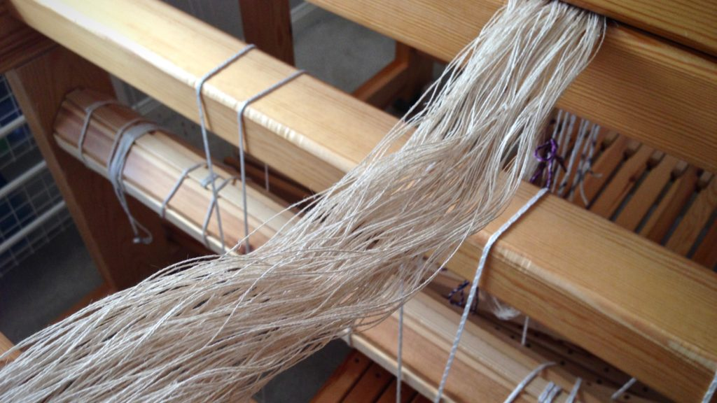 Preparing to beam a linen warp.