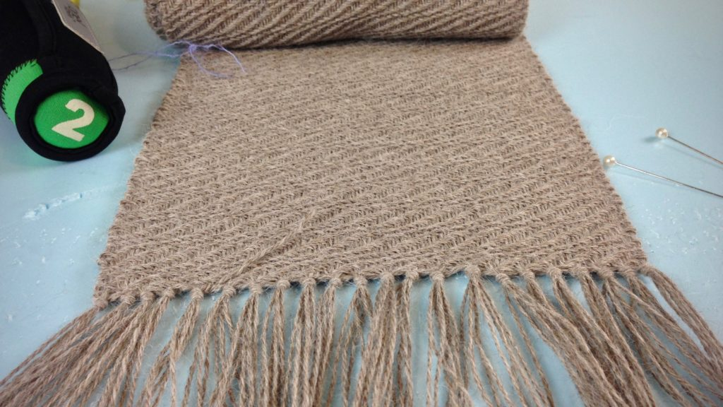 Finishing ends on a long handwoven alpaca scarf.