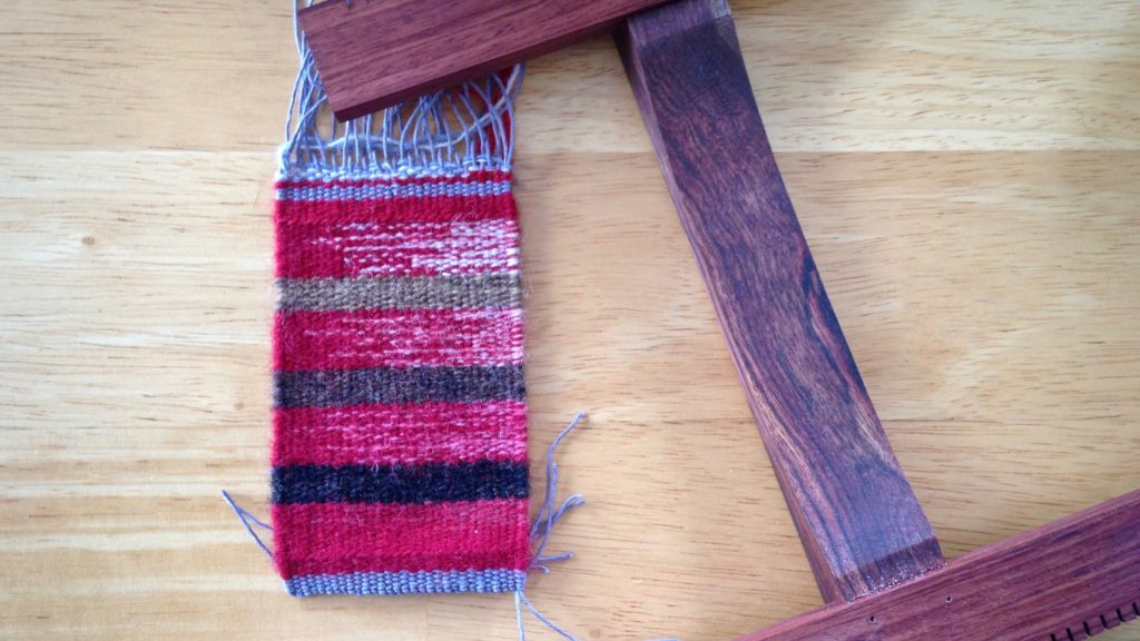 Hokett loom and small woven piece. Finishing in progress.