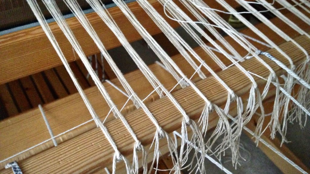 Adding the leveling string to a linen warp.