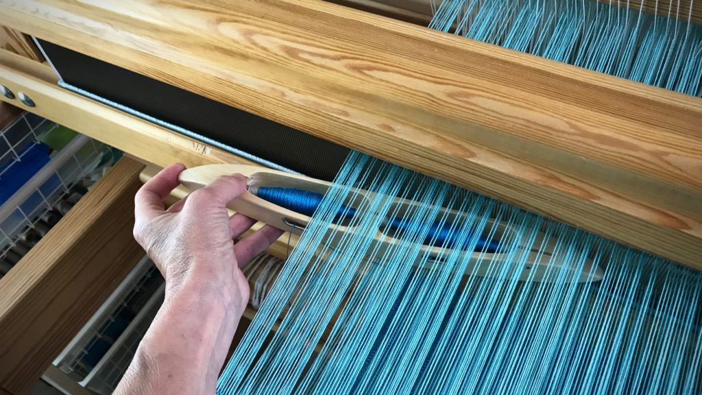Weaving with a double-bobbin shuttle.
