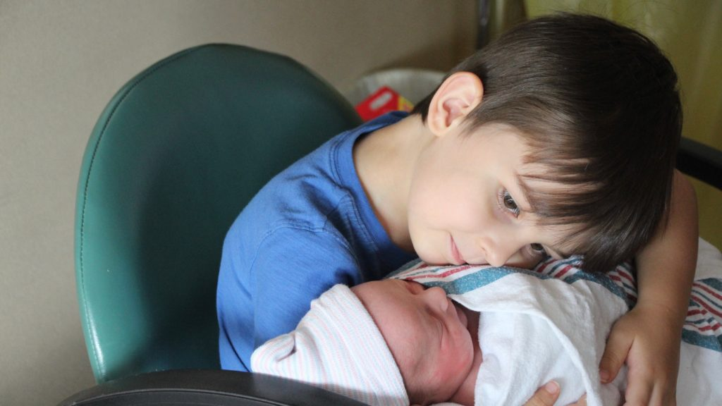 Big brother loving his new baby brother. Awww... so sweet.