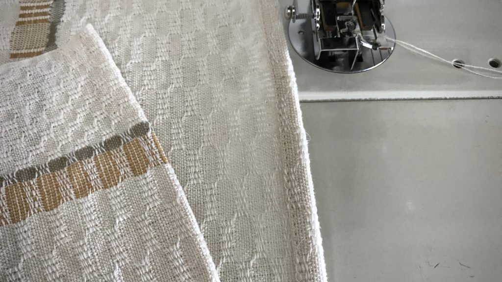 Hemming handwoven towels.