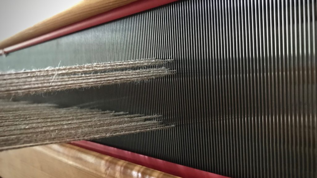 Adjusting treadles on countermarch loom.