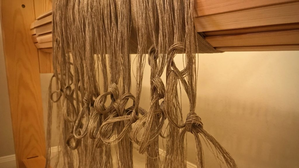 Beamed linen warp. Tied into threading groups.