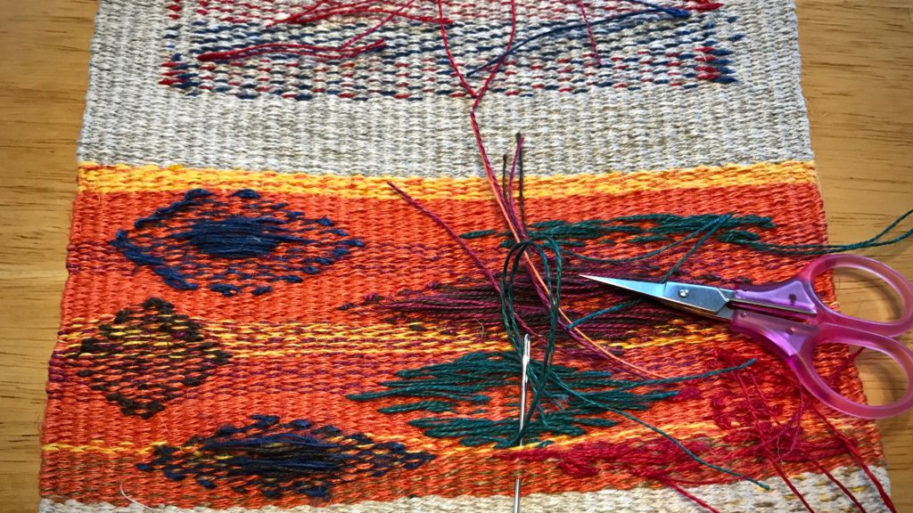 Sewing in weft tails in the back of a tapestry.