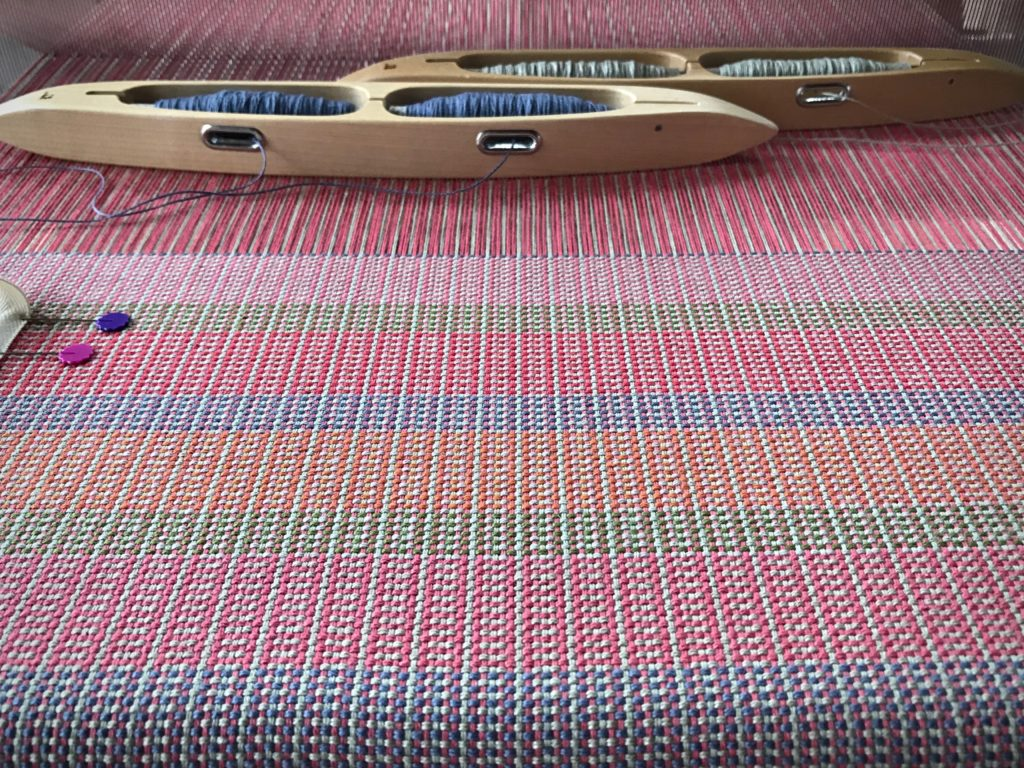 Two double-bobbin shuttles with color and weave.