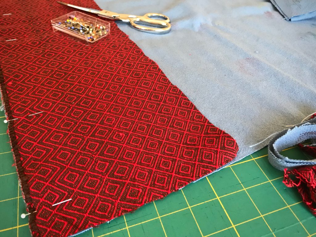 Piecing handwoven fabric to make a large bag.