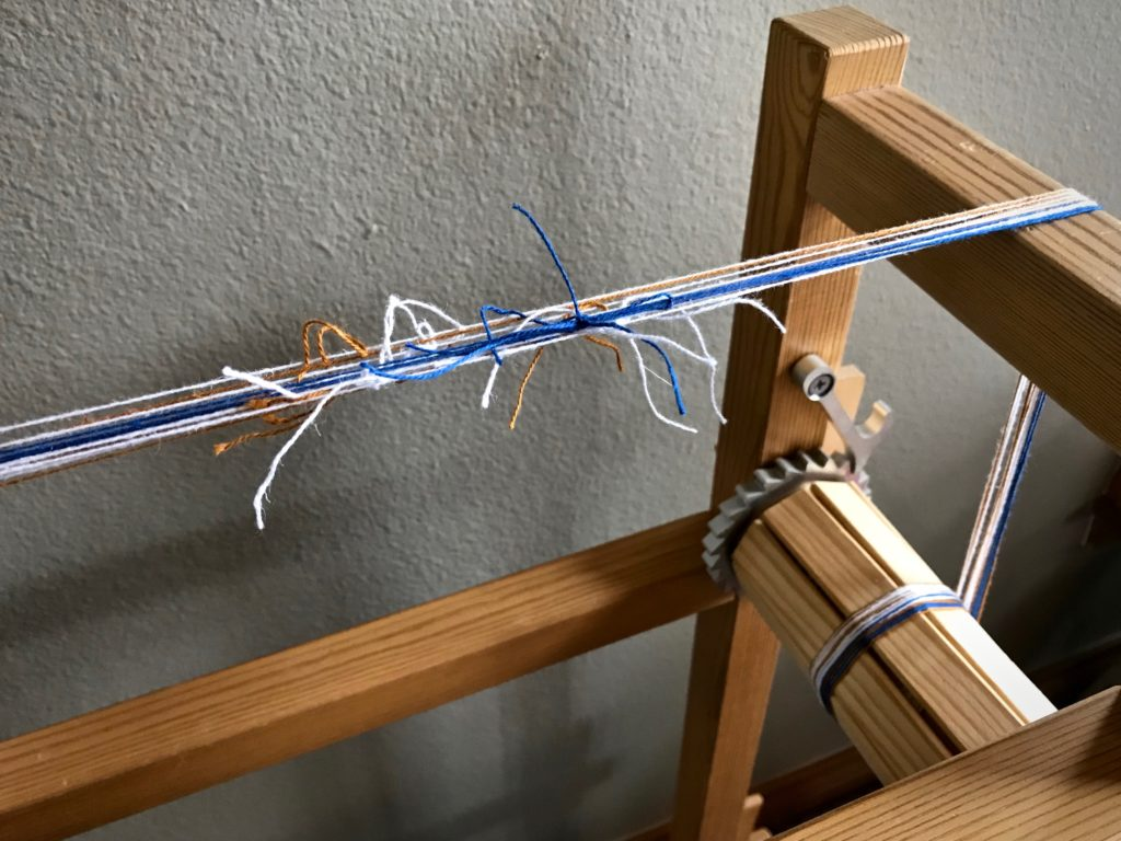 Thrums are used to make a warp for the Glimåkra band loom.