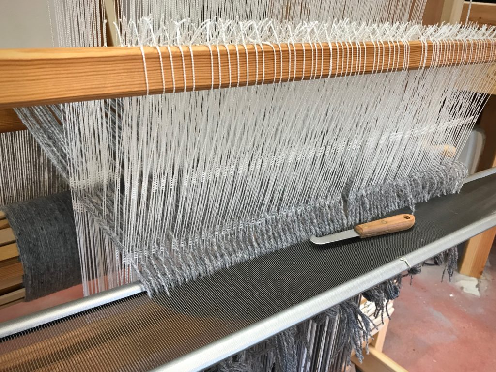 Sleying the reed on the drawloom.